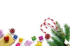 Rama de un árbol de navidad con las bolas, los conos de abeto, los caramelos tradicionales y las cajas con los regalos aislados e Fotografía de archivo