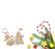 Rama de un árbol de navidad con las bolas, los conos de abeto, los caramelos tradicionales y las cajas con los regalos aislados e fotografía de archivo libre de regalías
