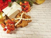 rama de un árbol de navidad, una pared de piedra, un árbol de navidad, una caja de regalo, una baya Fotos de archivo libres de regalías