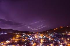 Rama de una luz del rayo una ciudad en la noche fotos de archivo