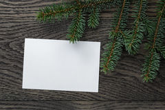 Rama del abeto con la tarjeta de papel en la tabla de roble desde arriba Imagen de archivo libre de regalías