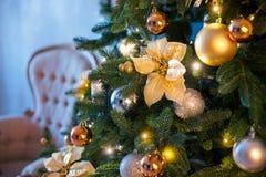Rama del abeto con las bolas y las luces festivas en el fondo de la Navidad con las chispas Foto de archivo