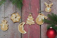 Rama del abeto con las decoraciones de la Navidad cerca de una pared de madera con las galletas de la Navidad Imágenes de archivo libres de regalías