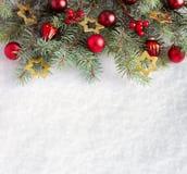 Rama del abeto con las decoraciones de la Navidad en el fondo de la nieve natural Imagenes de archivo