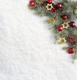 Rama del abeto con las decoraciones de la Navidad en el fondo de la nieve natural Foto de archivo libre de regalías