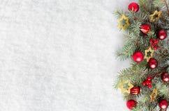 Rama del abeto con las decoraciones de la Navidad en el fondo de la nieve natural Imágenes de archivo libres de regalías