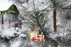 Rama del pino con un juguete de la Navidad en el fondo de un pueblo Fotografía de archivo