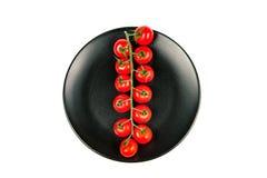 Rama larga de los tomates de cereza frescos maduros orgánicos en una placa negra aislada en un fondo blanco Visión superior Fotografía de archivo