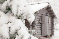 Rama nevada del abeto en un fondo de la choza Fotos de archivo