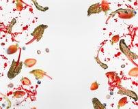 Rama różnorodne jagody z czerwonymi chard liśćmi i pluśnięcie sok na bielu latające lub spadają zdjęcie stock