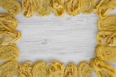 Rama różnorodny uncooked pastafettuccine, pappardelle, tagliolini na białej drewnianej powierzchni, odgórny widok Mieszkanie niea zdjęcie royalty free