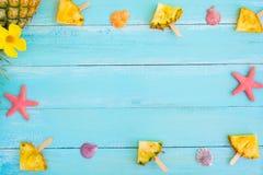 Rama robić ananasowi popsicle kije, rozgwiazda i skorupy, na drewnianej deski błękitnym kolorze Obrazy Royalty Free