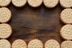Rama round ciastko kanapka z kokosowym plombowaniem na ciemnego brązu drewnianej powierzchni Niezwykły use ciastka jako rama E Fotografia Stock