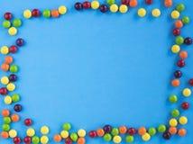 Rama stubarwny mały candie na błękitnym tle Odbitkowa przestrzeń dla teksta Mieszkanie nieatutowy Odgórny widok Obraz Stock