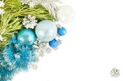 Rama y conos de árbol de abeto con las bolas y la malla azules encendido Foto de archivo libre de regalías