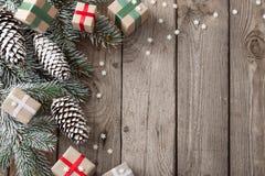 Rama y regalos verdes de la Navidad en fondo de madera foto de archivo