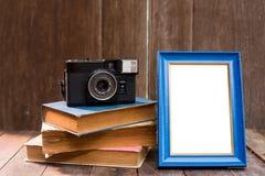 Rama z starymi książkami i starą kamerą na drewno stole Obrazy Stock
