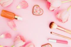 Rama z tulipanów kwiatami i kosmetykami, ciastka na różowym pastelowym tle Mieszkanie nieatutowy, odgórny widok z kopii przestrze zdjęcia royalty free