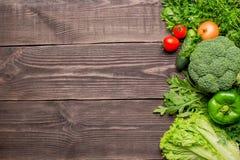 Rama zieleń i czerwoni świezi warzywa na drewnianym tle, odgórny widok obraz stock