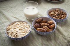 Ramadan and arabic or north african gatherings and breakfasts. Tea, milk, almonds, nuts and dates on bowls and glasses on a green fabric table Royalty Free Stock Photos