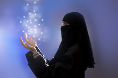 Ramadan: Beautiful young muslim girl praying, spirituality. Ramadan: Beautiful young muslim woman with hijab and jewelry praying, spirituality light Stock Images