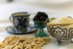 Ramadan break fast. Iftar glass of water and black dates on bread and cup on tea plus wheat and rice Royalty Free Stock Images