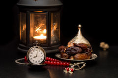 Ramadan concept with dates, pocket watch, rosary and lantern stock photography