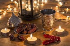 Ramadan concept with dates, rosary, and metal water cup with Allah text in arabic. On wooden table royalty free stock images