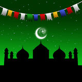 Ramadan Eid Garland. Eid illustration with a festive and colorful garland in a magic night scene with a mosque silhouette and the moon and stars on a green night Stock Photos