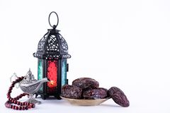 Ramadan food and drinks concept. Ramadan Lantern with arabian lamp, wood rosary, dates fruit and lighting on white background stock photos