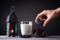Ramadan food and drinks concept. Woman hand reaches out to a plate with date with Ramadan Lantern with arabian lamp, wood rosary,. Tea, dates fruit and lighting royalty free stock photos
