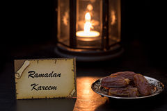 Ramadan kareem card with dates and lantern. In darkness Royalty Free Stock Photos