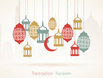 Ramadan Kareem celebration with hanging Arabic lanterns.. Hanging colorful Arabic lamps or moon on Islamic Mosque silhouette background for holy month of Muslim