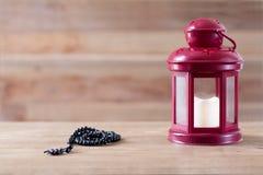Ramadan Kareem-/Eid Mubarak Electric Lamp- und Gebetsperlen mit hölzernem Hintergrund Stockfoto