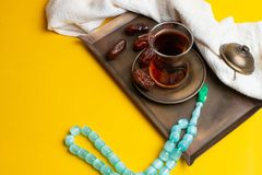 Ramadan Kareem Festival, Dates on wooden bowl with cup of black tea and rosary on yellow background royalty free stock images