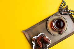 Ramadan Kareem Festival, Dates on wooden bowl with cup of black tea and rosary on yellow background stock images