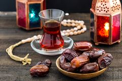 Ramadan Kareem Festive, close up of dates on wooden plate and ro. Sary with oriental Lantern lamps and cup of black tea on wood background. Islamic Holy Month Stock Photos