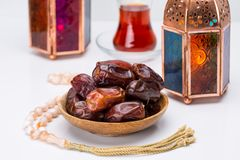 Ramadan Kareem Festive, close up of dates on wooden plate and ro. Sary with oriental Lantern lamps and cup of black tea on white background. Islamic Holy Month Stock Photos
