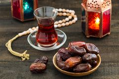 Ramadan Kareem Festive, close up of dates on wooden plate and ro. Sary with oriental Lantern lamps and cup of black tea on wood background. Islamic Holy Month Royalty Free Stock Photos