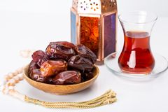 Ramadan Kareem Festive, close up of dates on wooden plate and ro. Sary with oriental Lantern lamps and cup of black tea on white background. Islamic Holy Month Royalty Free Stock Photos