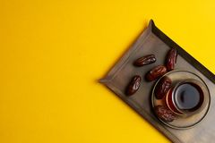 Ramadan Kareem Festive, Dates on plate and cup of black tea on yellow background royalty free stock photography