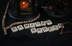 Ramadan Kareem Greeting Scrabble Letters. Ramadan Candle Lantern. With Wooden Prayer Beads and Dates Royalty Free Stock Photos