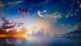 Ramadan Kareem religious background with mosque silhouettes reflected in serene sea stock photography