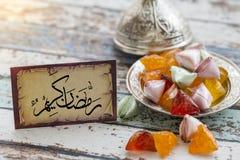 Ramadan kerim text in arabic on vintage table with candies. On metallic plate Stock Photos