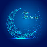 Ramadan mubarak greeting card.Shiny decorated crescent moon with stylish text Eid Mubarak on blue background Stock Image
