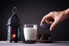 Ramadanmat och drinkbegrepp Kvinnahanden n?r ut till en platta med datumet med Ramadan Lantern med den arabiska lampan, tr?radban royaltyfria foton