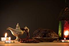 Ramadanvoedsel en drankenconcept Ramadan Lantern met Arabische lamp, houten rozentuin, thee, datafruit en verlichting op een hout royalty-vrije stock afbeeldingen