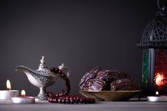 Ramadanvoedsel en drankenconcept Ramadan Lantern met Arabische lamp, houten rozentuin, thee, datafruit en verlichting op een hout stock foto's