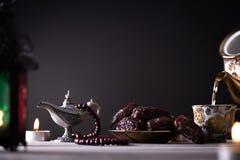Ramadanvoedsel en drankenconcept Ramadan Lantern met Arabische lamp, houten rozentuin, thee, datafruit en verlichting op een hout royalty-vrije stock afbeelding