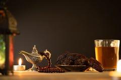 Ramadanvoedsel en drankenconcept Ramadan Lantern met Arabische lamp, houten rozentuin, thee, datafruit en verlichting op een hout royalty-vrije stock fotografie